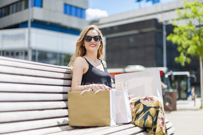 Portrait of smiling young woman sitting on a bench with shopping bags — Stock Photo