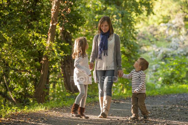 Mãe andando com seus filhos na trilha da floresta — Fotografia de Stock