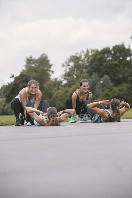 Four women doing sit-ups during outdoor boot camp workout — Stock Photo