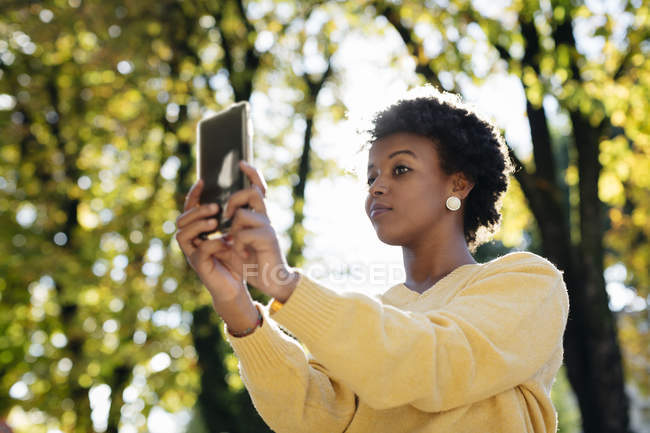 Schöne schwarze Frau mit Smartphone, outdoor im Herbst — Stockfoto