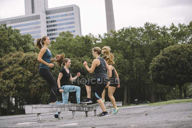 Cuatro mujeres con ejercicio al aire libre - foto de stock