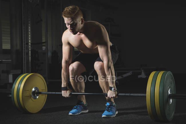 Фізичні спортсмена важкої атлетики зі штангою в тренажерний зал — Stock Photo