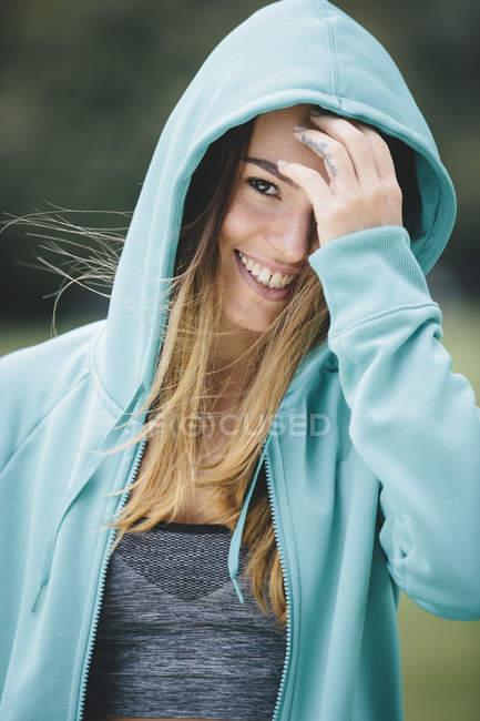 Souriant jeune femme sportive à capuche — Photo de stock