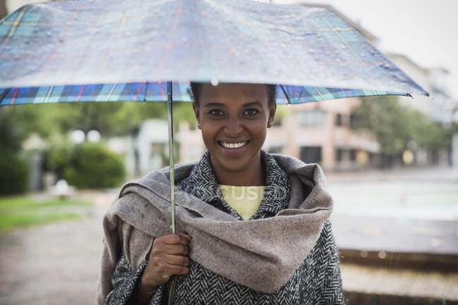 Retrato de mulher sorridente com guarda-chuva em um dia chuvoso — Fotografia de Stock