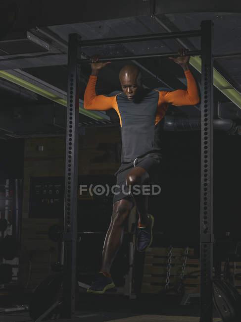 Физический спортсмен, занимающийся брюшной тренировкой на силовой стойке — стоковое фото