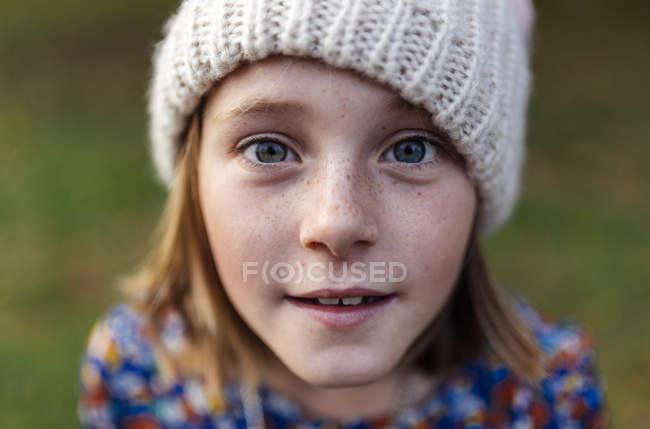 Retrato de una chica sonriente con gorra de lana mirando a la cámara - foto de stock