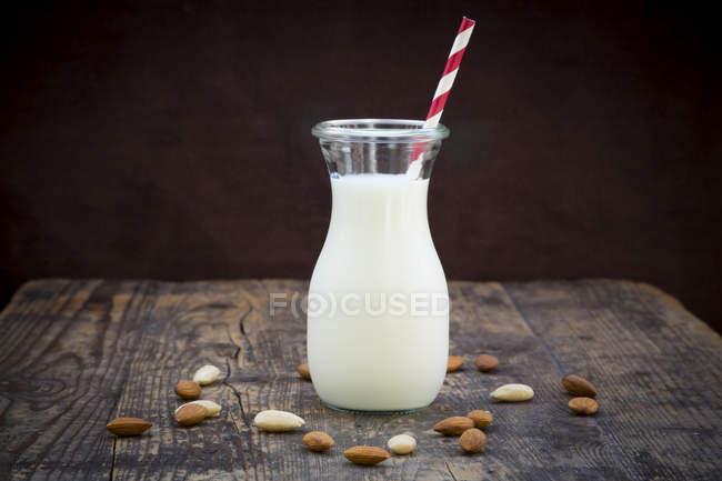 Latte di mandorla in brocca con cannuccia da bere su legno scuro con mandorle — Foto stock