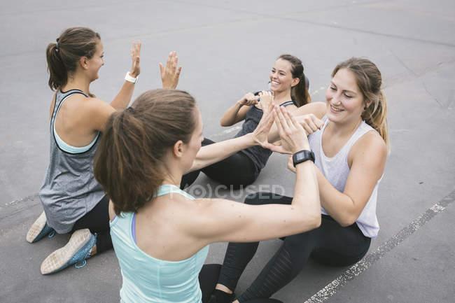 Чотири жінки, які роблять присідань під відкритий boot camp тренування — стокове фото
