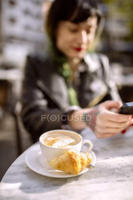 Coupe de cappucino, jeune femme en arrière-plan en utilisant le téléphone intelligent — Photo de stock