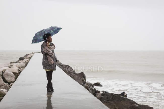Mulher com guarda-chuva em um dia chuvoso olhando para o mar — Fotografia de Stock