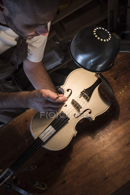 Luthier вивчення звукові повідомлення без прикрас скрипка в його майстерні — стокове фото