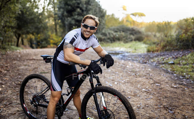 Portrait of smiling mountain biker driving in nature — Stock Photo