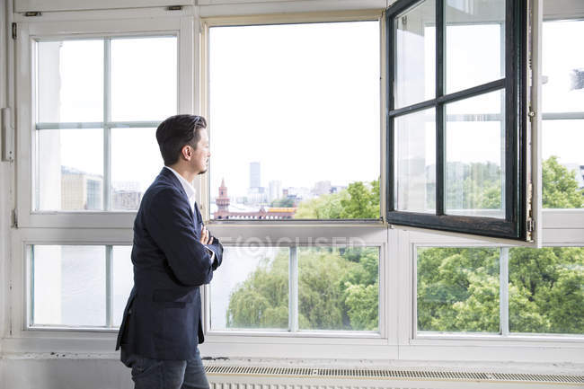 Businessman standing at open window with arms crossed — Stock Photo