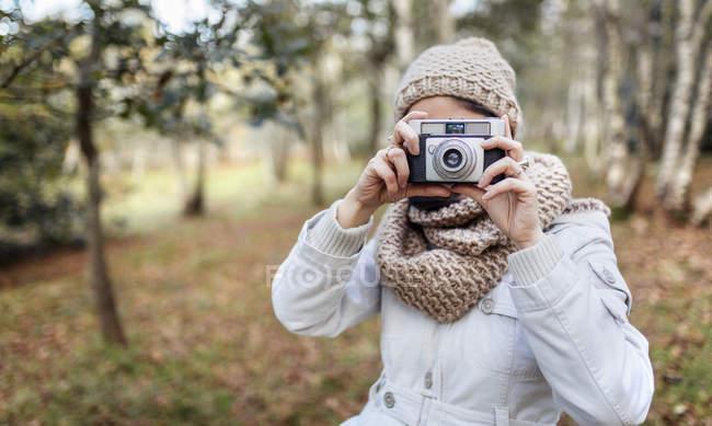 Женщина фотографирует в лесу — стоковое фото
