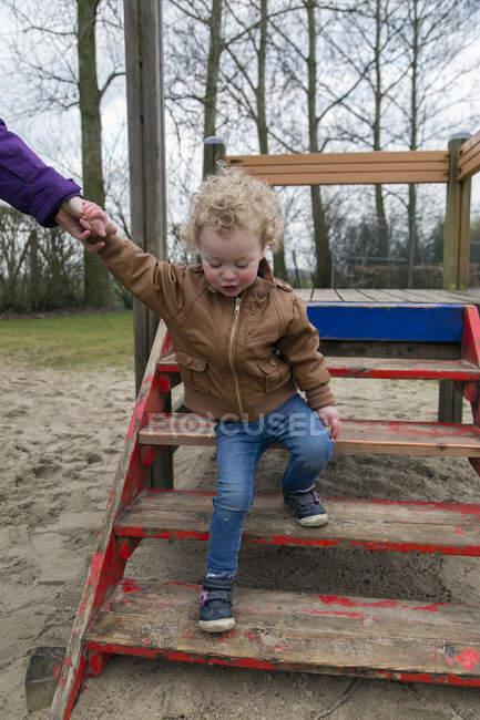 Mutter, Töchterchen, Spielplatz Treppen hinunter zu helfen — Stockfoto