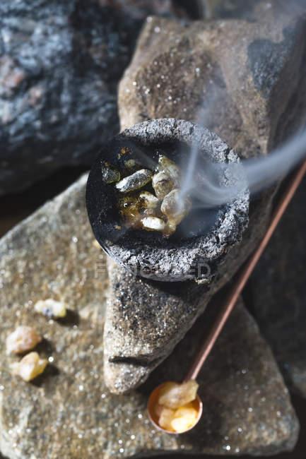 Burning incense over stone surface — Stock Photo