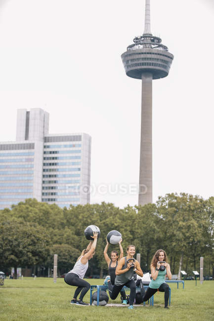 Cuatro mujeres que tienen al aire libre campo entrenamiento con kettlebells y bola - foto de stock