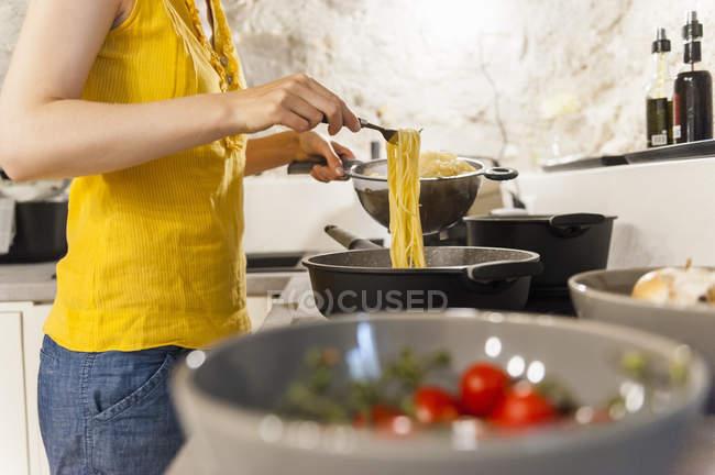 Mujer en cocina preparando espaguetis - foto de stock