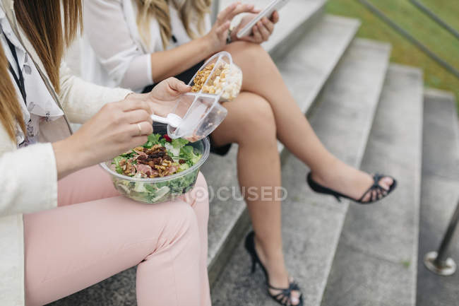 Cropped view of two women having lunch break on staircase — Stock Photo