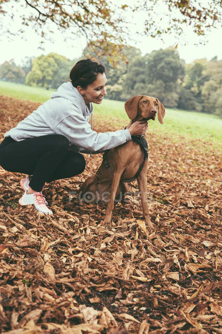 Woman talking to her Vizsla dog in park during autumn — Stock Photo