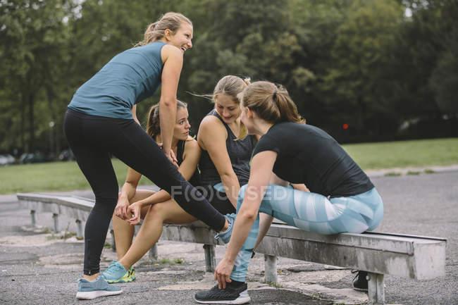 Четыре улыбающиеся женщины расслабляются после тренировки — стоковое фото
