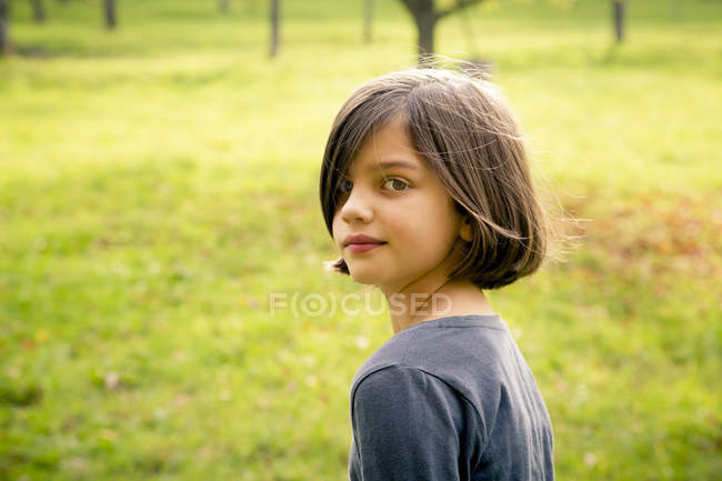 Портрет девушки, глядя на камеру через плечо — стоковое фото