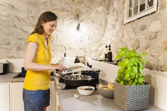 Mujer en cocina preparando salsa de espaguetis - foto de stock