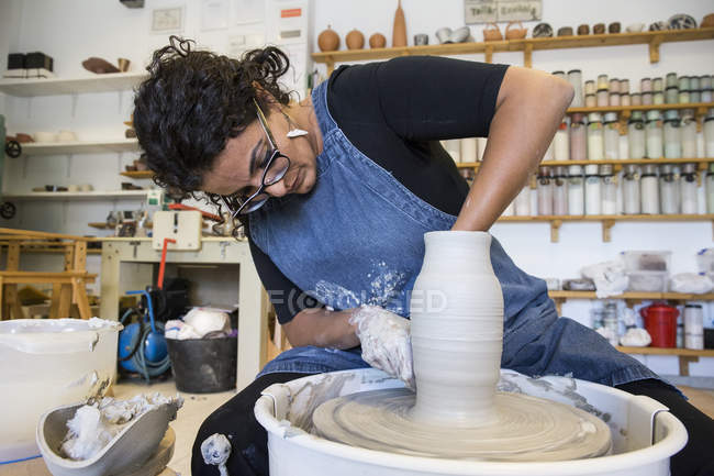 Woman working with pottery wheel in workshop — Stock Photo
