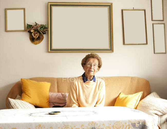 Portrait of aged woman sitting on couch in her living room — Stock Photo