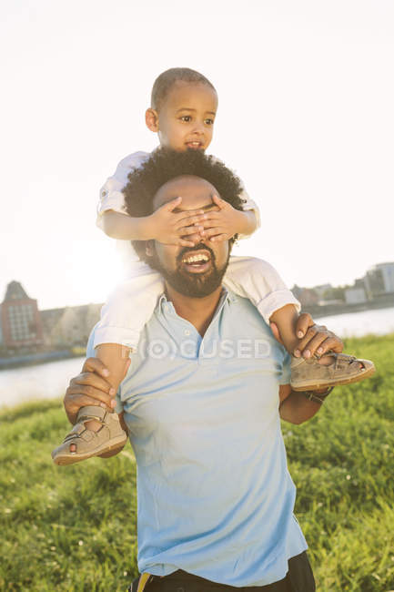 Happy african american father carrying his son on shoulders — Stock Photo