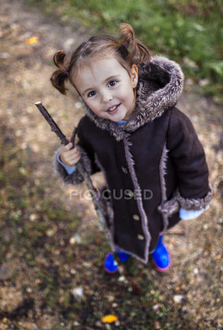 Portrait of smiling little girl in autumn looking up to the camera — Stock Photo