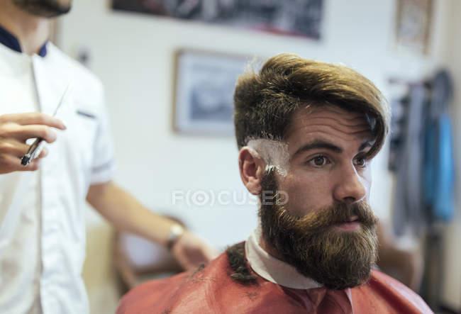 Customer with full beard sitting in a barbershop — Stock Photo