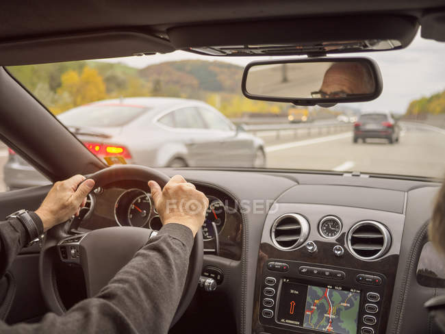 Close-up of senior man driving car on motorway — Stock Photo