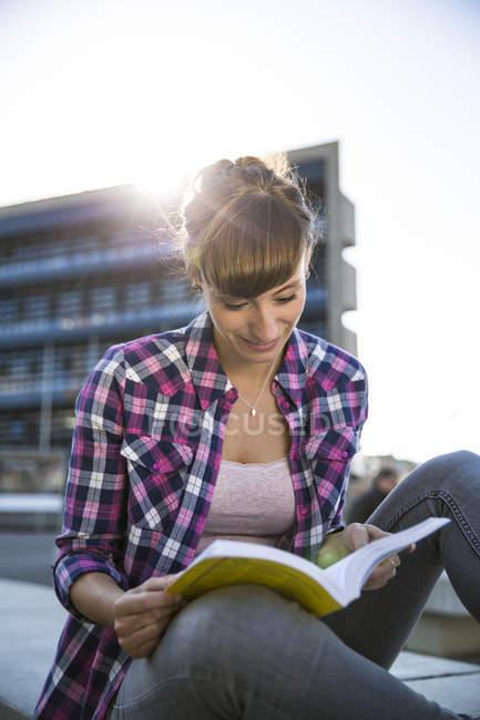 Junge Frau sitzt am Abend ein Buch zu lesen — Stockfoto