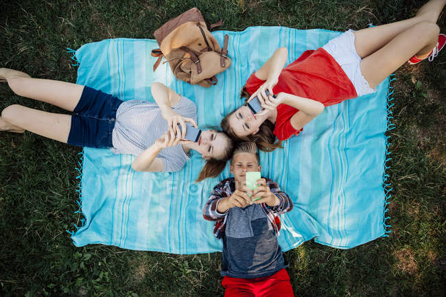 Three teenage friends with smartphones lying on blanket — Stock Photo