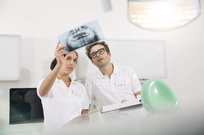 Two dentists in dental surgery discussing x-ray image — Stock Photo