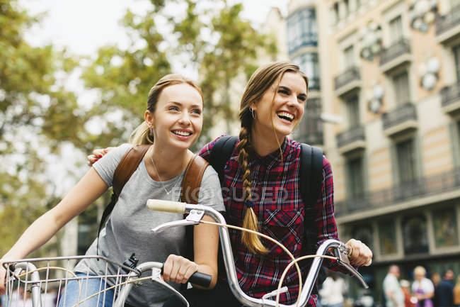 Две молодые женщины на велосипедах в городе — стоковое фото