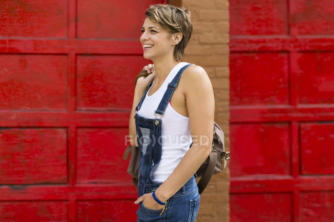 Smiling blond woman wearing jeans dungarees in front of red background — Stock Photo