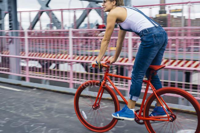 Соединенные Штаты Америки, New York City, Williamsburg, woman riding red racing cycle on Williamsburg Bridge — стоковое фото