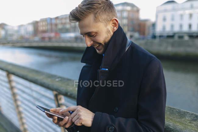 Irlanda, Dublino, giovane uomo d'affari sorridente che guarda il suo smartphone — Foto stock