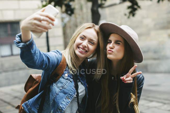Due giocose giovani donne che si fanno un selfie in città — Foto stock