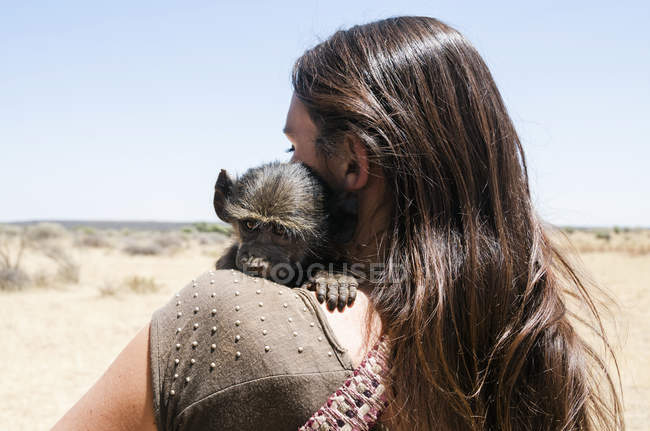 Namibia, close-up of woman holding baby baboon — Stock Photo