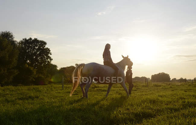 Young woman riding on horse, friend leading — Stock Photo