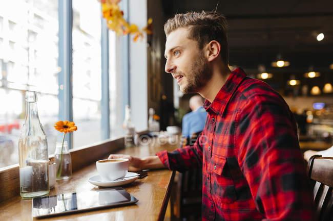 Людина в кафе дивиться з вікна — стокове фото