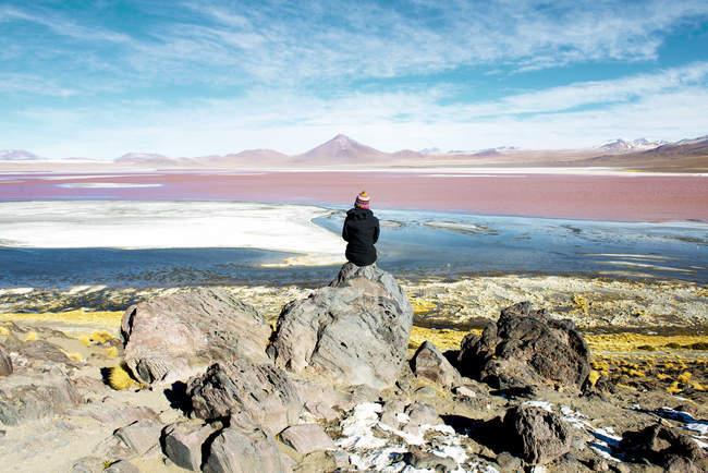 Donna di Bolivia, Potosi, ammirando la Laguna Colorada, stando seduti sulla roccia — Foto stock