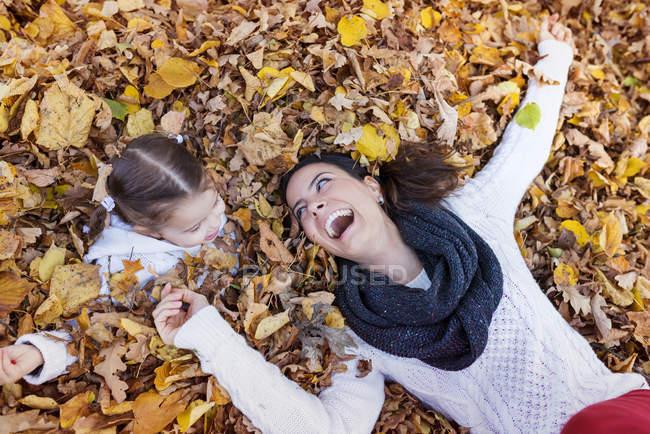 Счастливая девушка с матерью, лежащей в осенних листьях — стоковое фото