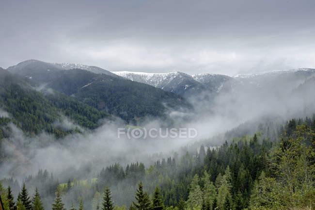 Австрия, Штирия, Мурау, заснеженные горы и туман в долине — стоковое фото
