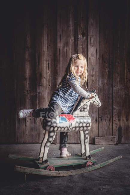 Portrait of little girl climbing on a vintage rocking horse in a barn — Stock Photo