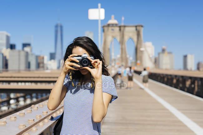 США, Нью-Йорк, молодая женщина, стоящая на Бруклинском мосту, фотографируется с камерой — стоковое фото