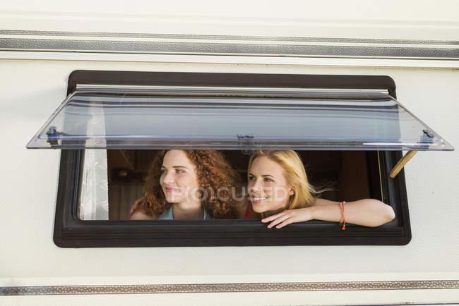 Dos amigas mirando por la ventana de la caravana mirando algo - foto de stock
